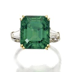 EMERALD AND DIAMOND RING, CARTIER. The emerald-cut emerald weighing 9.48 carats, flanked by tapered baguette diamonds weighing approximately .70 carat, mounted in 18 karat gold and platinum, size 5¾, signed Cartier, numbered HN446.
