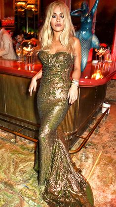 RITA ORA stunting in a gold sequined strapless gown at the launch of Sexy Fish, London.