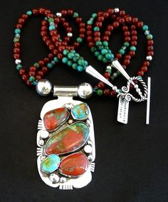 This striking Necklace showcases a 5-Stone custom Pendant by Nevada Silversmith Jim Daggett. The Pendant is 3-1/4 inches in length and features 3 large Sonora Sunset Stones in vivid tones of red and b