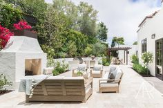 Alyssa Rosenheck - Amanda Barnes Interior Design - Chic patio features gray teak sofas and chairs lined with white cushions and gray pillows surrounding a gray teak coffee table facing a white stucco fireplace accented with a herringbone firebox.