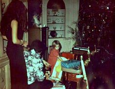 Elvis watching Lisa Marie unpacking Big Bird in the dining room at Graceland on Christmas morning.