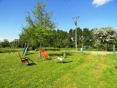Une partie du terrain à côté de la piscine avec transats pour se dorer au soleil tout en dégustant un bon verre et des balançoires pour les enfants.