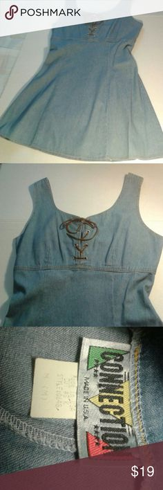 """Vintage denim dress by connection size medium You are viewing a super cute vintage light denim dress by Connection made In USA size medium. It is a lighter denim empire waist style w/ some fading due to its age. Cute w. Sneakers, boots or heels. Thin not heavy has a leather like string through the holes on top. You can relace or replace with ribbon etc once you get it. Can even wear with tights. Pit to pit about 17 1/2 + """" length ~32"""". Great dress, used but still has a lot of life in it…"""