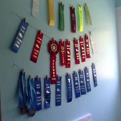 Simple and nice way to display ribbons, with just string and small wooden clips. Award Ribbon Display, Award Display, Swim Ribbons, Hanging Medals, Horse Show Ribbons, Ribbon Boards, Kids Awards, Trophy Display, Ribbon Wall