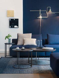 déco appartement, mur peint en blanc et bleu, table basse en noir, canapé en bleu foncé, lampe industriel blanche