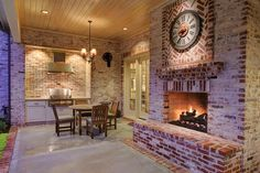 3506 Suffolk Dr Houston, TX 77027: Photo The covered loggia has a concrete floor with brick inlay, Isokern fireplace with has logs, Oscillating wall fans, outdoor chandelier, and a infra-red gas grill with professional style exhaust fan.