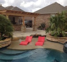 A pair of red Ledge Loungers really make their mark in this freeform pool with a large tanning ledge. http://www.luxurypools.com/blog/entryid/107/in-pool-chaise-lounges-designed-for-tanning-ledges.aspx#