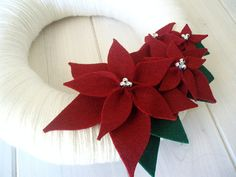 Beautiful way to welcome the holiday season! This wreath is wrapped in a snow white yarn with a cluster of poinsettia flowers and leaves.. perfect for the season! Great on your front door, in your kitchen or on your wall! Excellent gift for a new home, too! * This listing is for a 12 wreath as shown ****This wreath can also be made as a larger wreath! 14 Round $50 16 Round $65 Custom colors can be requested, convo me! ♥ This and every Itz Fitz! wreath is handmade and made t...