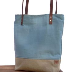 A European Linen Tote accented with beige burlap bottom, duck canvas interior and brown leather straps. This simple tote makes a great everyday spring bag. Exterior: Light Blue European Italian Linen;