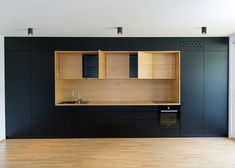 A fitted kitchen, a seating nook and a desk space are all contained in oak-lined recesses in the walls of this apartment in Ljubljana by Arhitektura d.o.o.