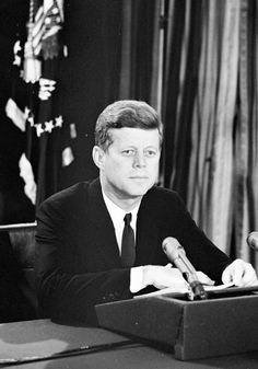 Our Presidents. President John F. Kennedy (seated at desk) delivers a radio and television address to the nation regarding the Soviet Union's military presence in Cuba. Oval Office, White House, Washington, D.C on October 22, 1962 (John F. Kennedy Library and Museum)