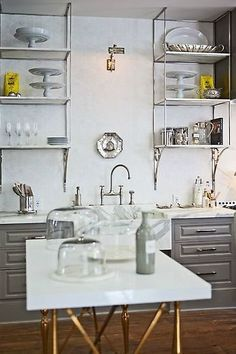 Out of the Ordinary: 10 Kitchens with Unique Open Shelving: It's the delicate brackets that make these shelves so interesting. This designer gets bonus point for perfectly matching the metal on the brackets to the faucet and hardware. Spotted on Bungalux.