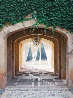 FOR THE CEREMONY || Stone aisle archway with rustic vine & chandelier || NOVELA...where the modern romantics play & plan the most stylish weddings...Instagram: @novelabride www.novelabride.com