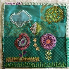 Embroidery sampler with flowers and a kite on a patchwork background.