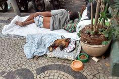 (Foto: Facebook / Jaqueline Winter) - Morador de rua no RJ acolhe um cão com cama, cobertor, ração e água, é uma ação linda e comovente!