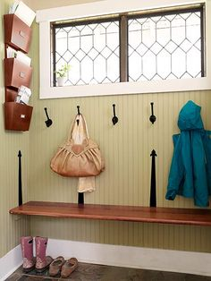 This beadboard-lined mudroom has bins for mail and a bench made from a stair tread supported by cleats and finished with decorative iron straps. See more of this fabulous home here.