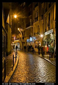 Cobblestone street with restaurants by night. Quartier Latin, Paris, France