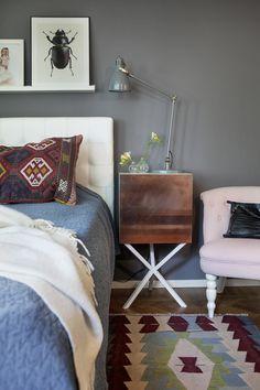 Sovrummet har skönt mörkgrå väggar. Lampa Ikea, fåtölj, Myrorna i Skärholmen, väska Little Liffner, nattduksbord Per Söderberg NEB, matta och kudde från Bodrum Turkiet, sänggavel Sänghuset Elgen, överkast Ikea, vaser H&M Home, tavla Liljebergs.