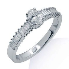 Simply stunning! Handcrafted in lustrous 18k white gold, this ring features a simple yet elegant design with baguette cut diamonds in a channel setting leading up to the beautiful oval cut diamond held in a secure 4 prong setting. The color of the diamonds are G/H and the clarity is SI2/SI3. $1,225.00 Diamond Promise Rings, Baguette, Clarity, Channel, Diamonds, White Gold, Engagement Rings, Elegant, Simple