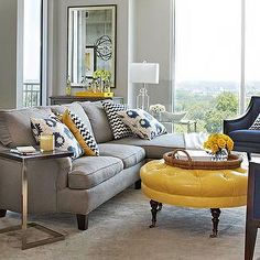 A navy accent wall, cream curtains, grayish brown couch. Accents of yellow (yellow chair or ottoman) with navy, cream and yellow accent pillow. Navy and cream area rug. Warm cream baseboard etc and greyish brown walls.
