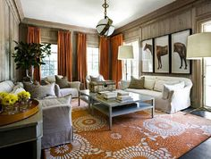 Love this room! Love the wood walls, the equestrian print on the wall, and the orange curtains!