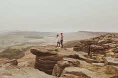 Couple stood on the top of the cliff at Stanage Edge, in the Sheffield & Derbyshire Peak District.