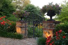 Free-standing stone & brick columns with urns create an attractive portal for an iron gate - no fence necessary...