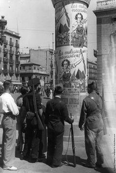 Es en España. Soldados lean el posters que llamando a las mujeres a luchar durante la Guerra Civil española.