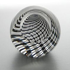 """Paul Harrie  The 1 5/8"""" facet on the side adds visual interest to this weight by Paul Harrie. The interior holds a sphere of clear glass that has been wrapped in black and white stripes."""