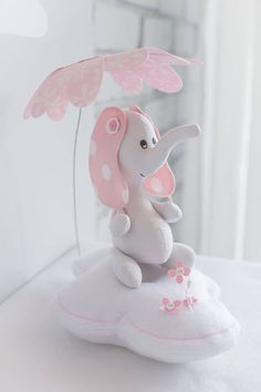 Baby elephant nursery décor in pink and grey colors. The little elephant is sitting on puffy cloud under fabric flower umbrella holding a tiny