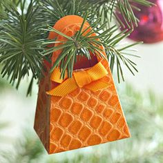 """Pretty Purse Ornament: Design by Pamela Porter: Using a die-cutting tool, cut out a purse shape from sturdy patterned paper or cardstock. Fold and assemble the purse and add a gem or ribbon bow for decorative trim.  Editor's Tip: If you can't find a heavyweight patterned paper you like, make lightweight paper sturdy by adhering it to plain cardstock using double-sided adhesive."""