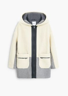 Faux shearling cocoon coat -  Women | MANGO. Sheepskin fabric, hood, long sleeve, contrasting panels, two side patch pockets, zipped pockets, zip fastening on the front section, contrasting inner lining.