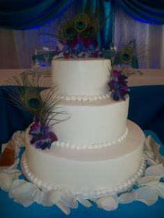 Three tier buttercream iced wedding cake for a Peacock themed wedding.  Accented with peacock feathers and Singapore orchids.