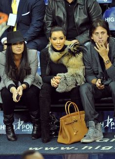 Kim Kardashian wearing Christian Louboutin Monica Over The Knee Boots American Apparel Baby Rib Long Sleeve Turtleneck Hermes 35cm Birkin Bag In Gold Feathers Fur Sleeve. Kim Kardashian At the Miami Heat vs NJ Nets Game October 31 2010.