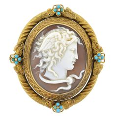 Victorian Carved Medusa Cameo Turquoise Gold Pin. This large French cameo is a hand-carved locket pin and pendant from the Victorian (ca1880) era! Set within an ornate 18kt yellow gold bezel setting, the profile of Medusa graces the center of the piece. The image is highly detailed, including intricate facial features, delicate wisps of hair, and serpents that are camouflaged within her hair and coiled at her neck. Resting at one side of her head is a small feathered wing that peaks out from…