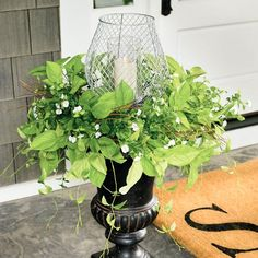 Bring everlasting life (and light) to a planter, in seconds, with our just-like-nature Spring Lantern Urn Filler. A beautiful end to watering and wilty foliage, and just the beginning of a long line of glowing reviews from guests. An abundant mix of seasonal favorites captures the essence of spring in spectacular fashion. Flowing green vines and leaves burst out from the base and are punctuated with delicate white flowers. In one brilliantly warm final touch, metal arbor surrounds a glass…