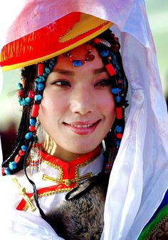 Very beautiful performer from the Lithang Horse Festival wearing turqoise and coral in her braided hair