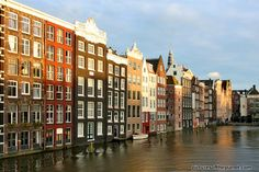 Evening photograph of tradional looking Amsterdam apartments and houses lining the side of a manmade canal. Check out the cornices on some of the buildings.
