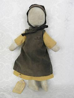 """Great Old Cloth Amish Faceless Doll Tagged Geneva Indiana 1950s 15"""". The tag says """" Geneva, Indiana Amish doll, circa 1950. Black thread is indicative of Indiana Amish """".Her cloth body appears to be rag stuffed. She has sewn on stump arms and legs. Some of the stitching is torn and there are old repairs as shown. Her body is age stained.The bonnet & apron have fading and there is soiling to her clothing. Amish Dolls, Guys And Dolls, Amish Country, Black Thread, Geneva, Antique Dolls, Doll Patterns, Indiana, Fashion Backpack"""