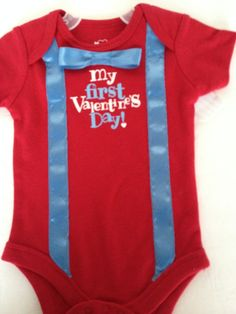 Silk screen printed boy's first Valentine's Day onsie with sewn on light blue satin ribbon suspenders and bow tie. Machine wash and dry.