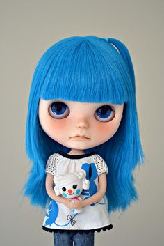 Blythe   Doll has blue hair  Dolls' facial expression is sad. She's holding a pet