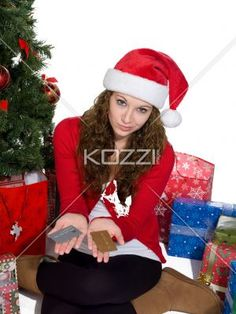 young woman displaying credit cards. - Portrait of a beautiful young woman displaying credit cards while sitting next to Christmas tree, Model: Brittany Beaudoin