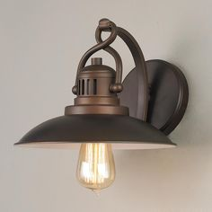 Station Lantern Sconce This contemporary adaptation of nostalgic hanging station lanterns is detailed with a twisted handle and vented housing for a wall light with both vintage and modern appeal in burnished Bronze. 1 x 100 watts max (medium base socket). Damp rated.