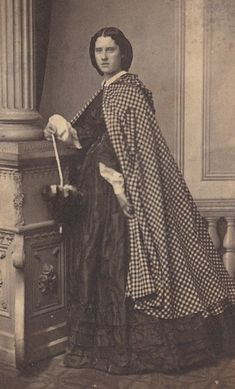 Checked plaid cape with decorative hood. Silk dress with high bodice, open sleeves, skirt with 3 ruffles at hem. Shown with collar, undersleeves, folding parasol.