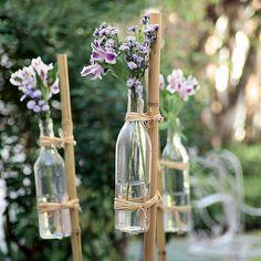 Garrafas, flores, bambus e ráfia: com esses quatro elementos, o jardim ganha cara de festa no ato. Você pode fazer um caminho com os arranjos ou espetar as varas aleatoriamente pela terra. Para garantir que o vidro não escorregue, amarre o vasilhame com f