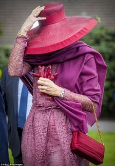 Queen Maxima struggled to keep hold of her hat in the windy weather at the event today