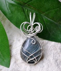 This pendant features a teardrop-shaped Labradorite stone that has been wrapped in Argentium silver wire. Beautiful hues of teal and mauve. Pendant