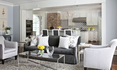 source: At Home in Arkansas    Gorgeous open living room design with dark gray slip-covered sofa, silver pillows, antique mirrored cocktail table, light gray linen accent chairs, gray & yellow rug, gray linen counter stools, exposed brick wall, white kitchen cabinets and blue walls paint color.  Sherwin Williams North Star decorpad.com