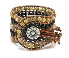 Semi precious stones of fire agate, mat onyx & mat jasper are framed by brown leather woven together with beige cotton cord. This eye catching design also features a silver metal, repousse, lightly oxidized, floral closure.This bohemian style bracelet upgrades your casual look.