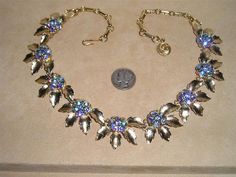 Dates- 1960s  Measurements- up to 16 inches in length, adjustable  Signed Lisner  Beautiful brushed gold tone necklace with blue iridescent crystal